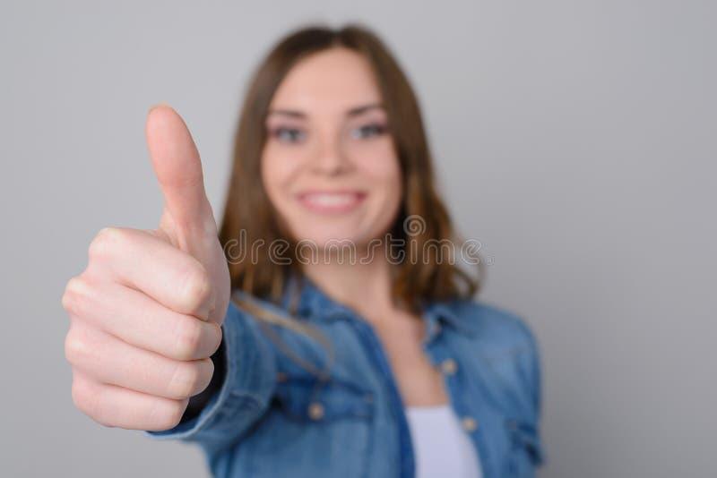 Feche acima da foto da mulher bonito feliz de sorriso na roupa ocasional que mostra o polegar acima É isolada no bom grande negóc imagens de stock