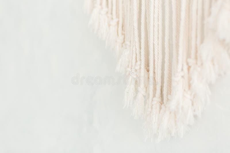 Feche acima da franja do painel do macramê do algodão em uma parede escandinava minimalistic Textura Fundo foto de stock royalty free
