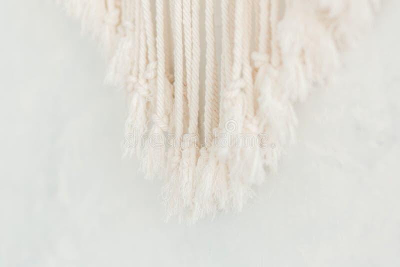 Feche acima da franja do painel do macramê do algodão em uma parede escandinava minimalistic Textura Fundo fotografia de stock