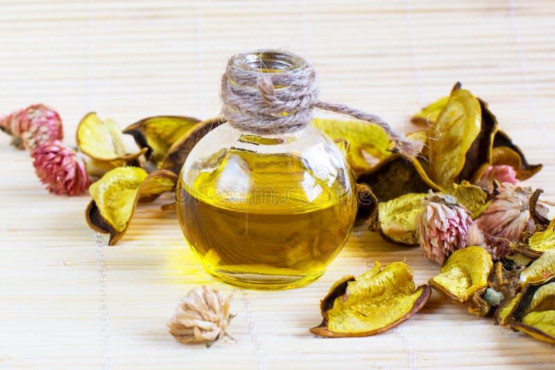 Feche acima da garrafa de óleo essencial ou cosmética com seco foto de stock royalty free