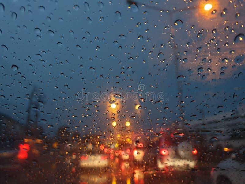 Feche acima da gota chuvosa no carro de vidro com luz da noite fotografia de stock