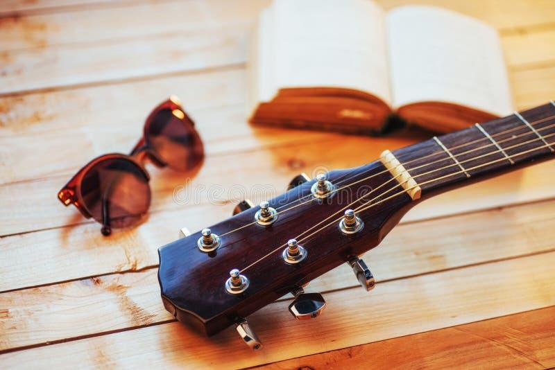 feche acima da guitarra clássica acústica do pescoço em um fundo de madeira claro imagem de stock royalty free