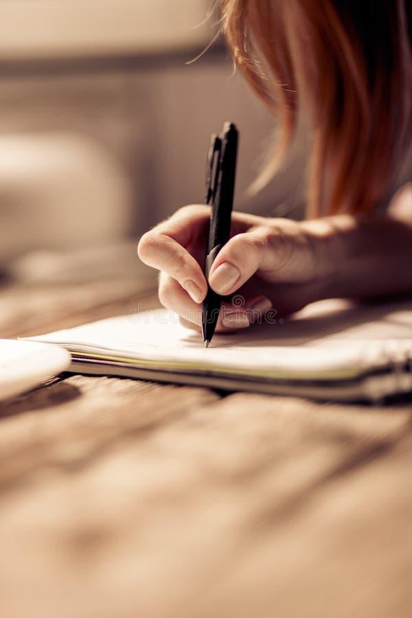Feche acima da ideia da escrita da mão da mulher no caderno foto de stock royalty free