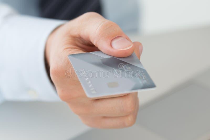 Feche acima da ideia da mão do homem de negócio que guarda o cartão de crédito imagem de stock royalty free