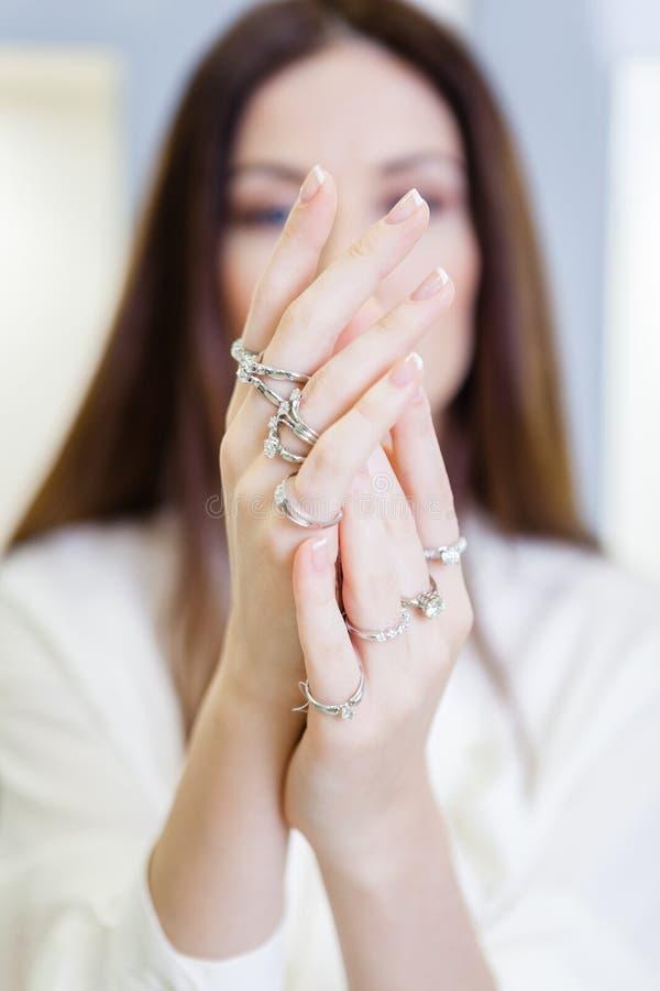 Feche acima da ideia das mãos fêmeas com anéis fotografia de stock royalty free