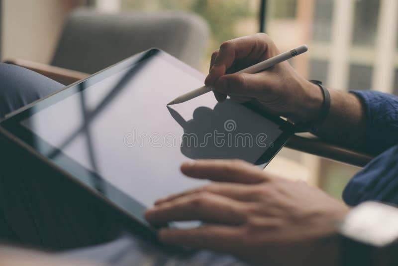 Feche acima da ideia das mãos masculinas que guardam a pena do estilete e que trabalham em uma tabuleta digital Fundo borrado hor fotografia de stock