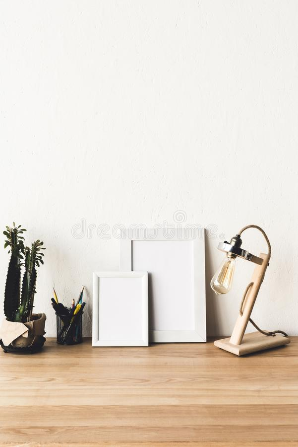 feche acima da ideia de quadros vazios da foto no tabletop de madeira com candeeiro de mesa e planta imagem de stock royalty free