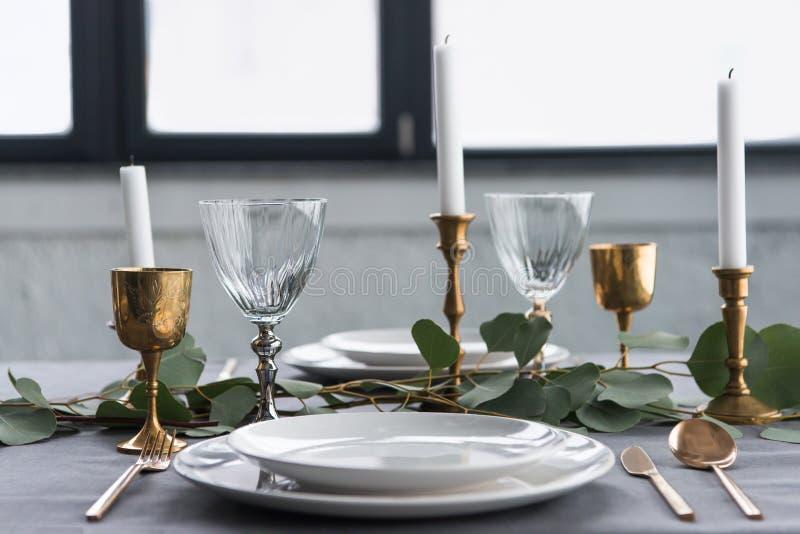 feche acima da ideia do ajuste rústico da tabela com vidros de vinho, eucalipto, cutelaria do vintage, velas nos castiçais e as p imagem de stock