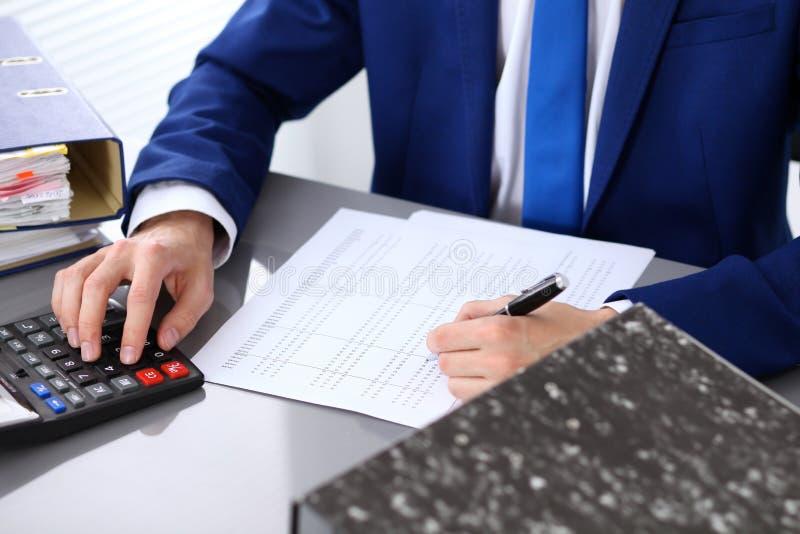 Feche acima da ideia do guarda-livros ou das mãos financeiras do inspetor que fazem o relatório, calculando ou verificando o equi foto de stock