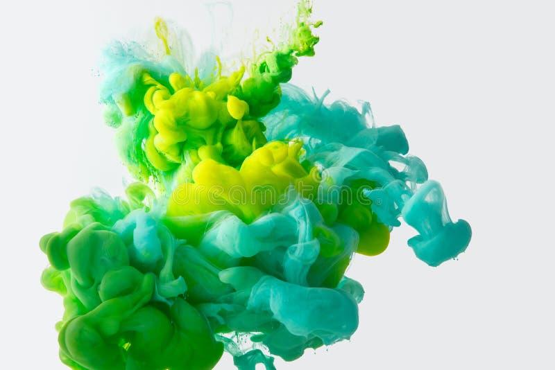Feche acima da ideia da mistura de verde, amarelo e as pinturas brilhantes de turquesa espirram na água isolada no cinza foto de stock