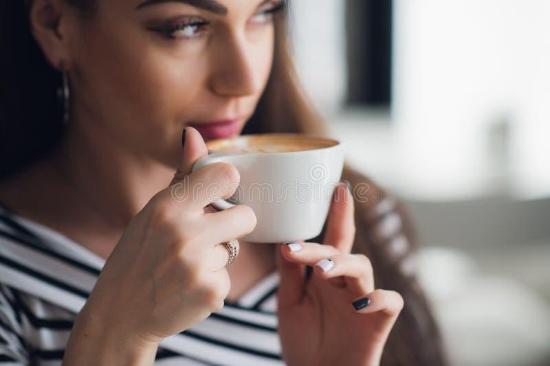 Feche acima da imagem das mãos que guardam um café bebendo do copo e da mulher dele foto de stock