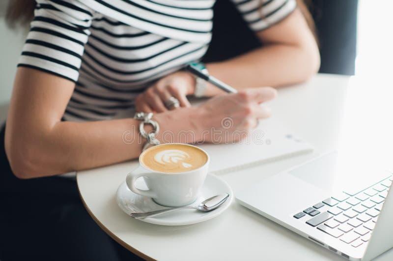 Feche acima da imagem de um copo do cappuccino com um teste padrão e as mãos que escrevem em um caderno Mulher que senta-se em um fotos de stock royalty free