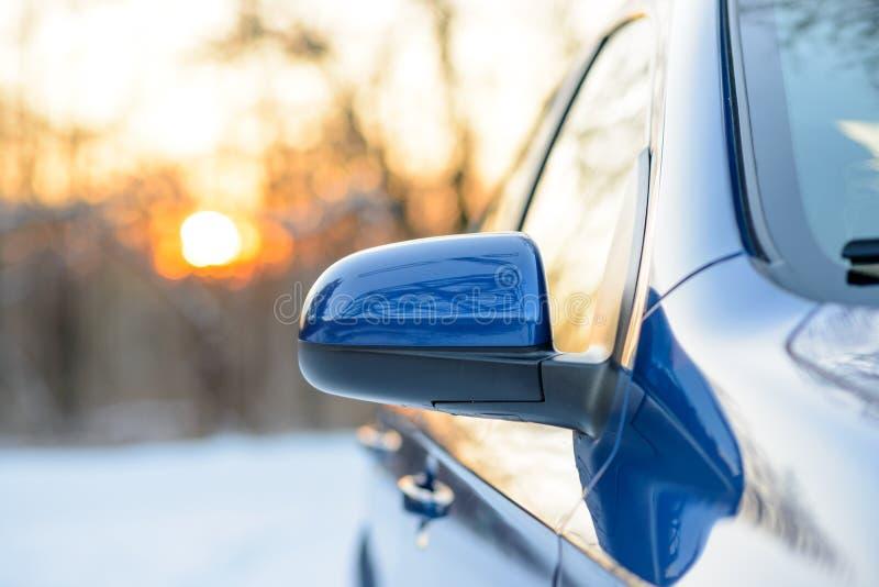Feche acima da imagem do espelho retrovisor lateral em um carro na paisagem do inverno com noite Sun imagem de stock royalty free