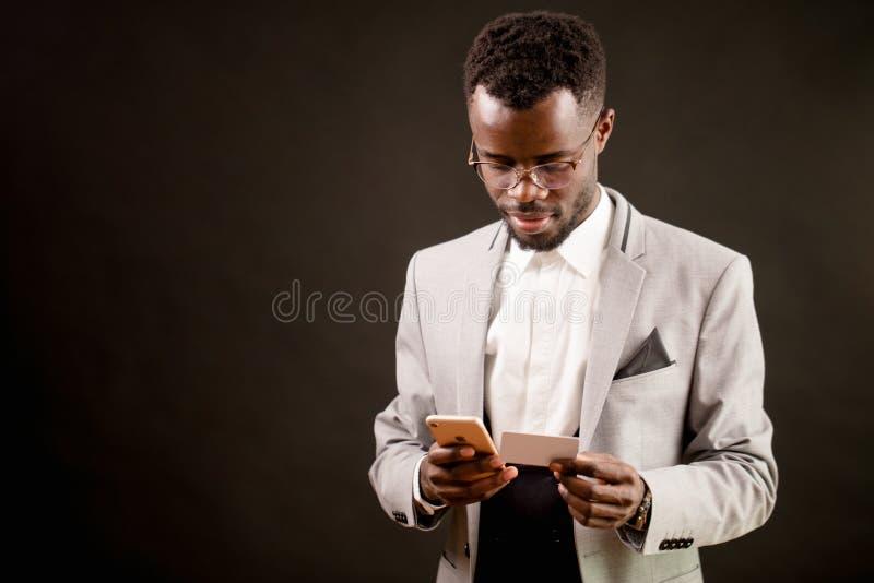 Feche acima da imagem do gerente africano que olha seus cartão e telefone celular de visita imagens de stock