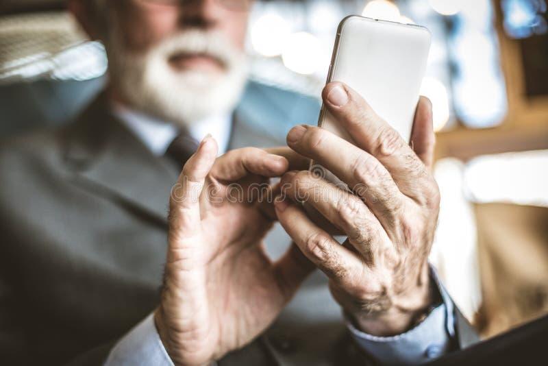 Feche acima da imagem do homem de negócios superior usando o telefone celular imagem de stock