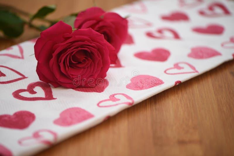 Feche acima da imagem da fotografia da flor de rosas vermelhas frescas em um pano vermelho e branco do teste padrão do coração do foto de stock