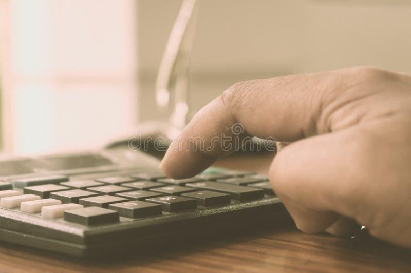 Feche acima da imprensa o botão direito Calculadora com dedo Dedos que pressionam os botões da calculadora Uma mão de datilografi imagens de stock