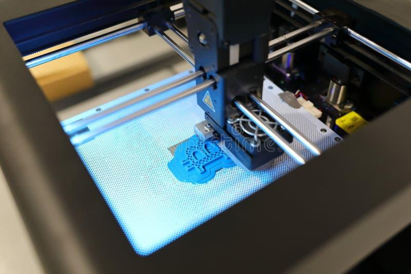Feche acima da impressora 3D ao imprimir o formulário azul do bitcoin imprimir 3D em andamento Nova geração de máquina de impress imagem de stock royalty free