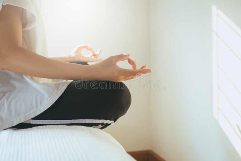 Feche acima da ioga e da meditação asiáticas das práticas da mulher das mãos na posição de lótus imagem de stock