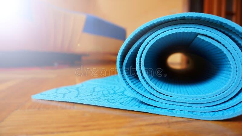 Feche acima da ioga, esteira do assoalho da aptidão em casa em um rolo Conceito saudável imagens de stock