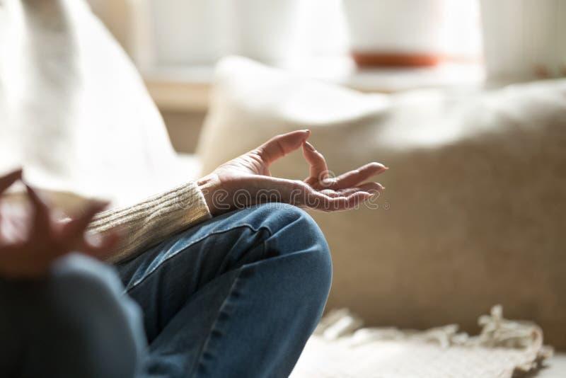 Feche acima da ioga praticando meditando fêmea da came em casa fotografia de stock royalty free