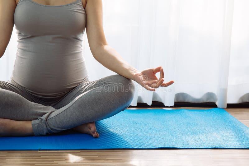 Feche acima da ioga praticando da mulher gravida nova imagens de stock royalty free