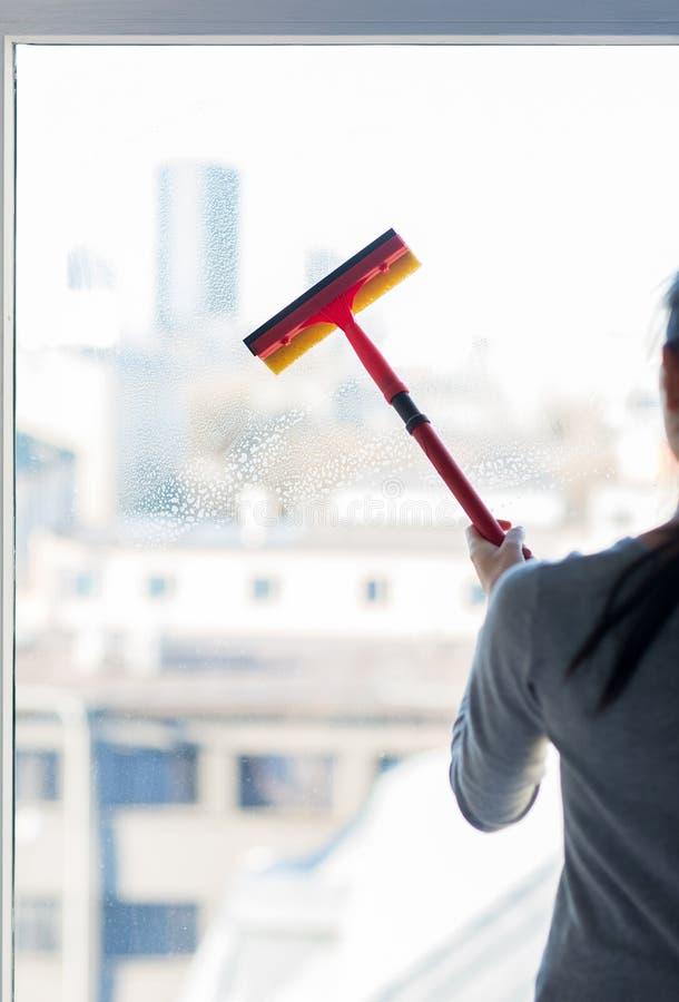 Feche acima da janela da limpeza da mulher com esponja fotografia de stock
