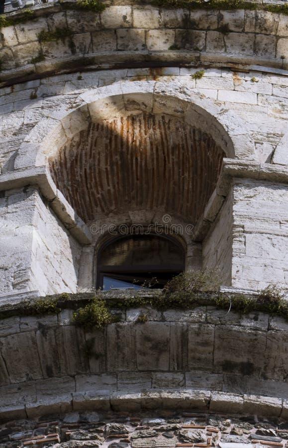 Feche acima da janela misteriosa de uma torre medieval da alvenaria imagem de stock