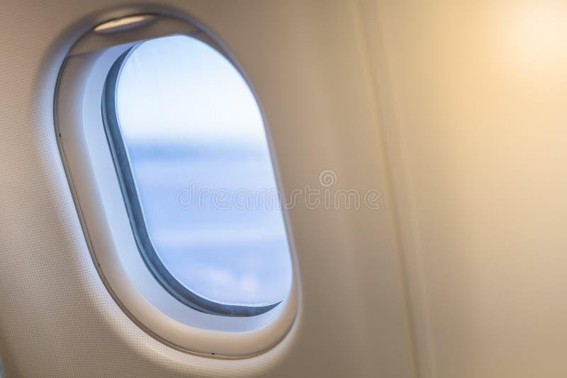 Feche acima da janela oval do avião com céu azul Conceito do transporte e do curso imagem de stock royalty free