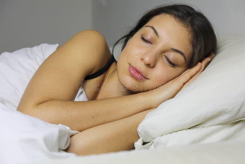 Feche acima da jovem mulher bonita que sorri ao dormir nela imagens de stock royalty free