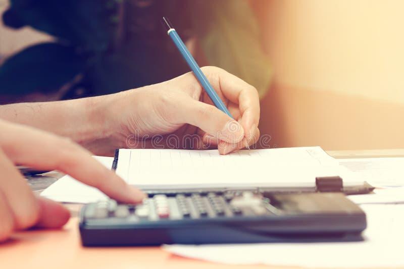 Feche acima da jovem mulher com a calculadora que conta fazendo anotações em ho fotografia de stock