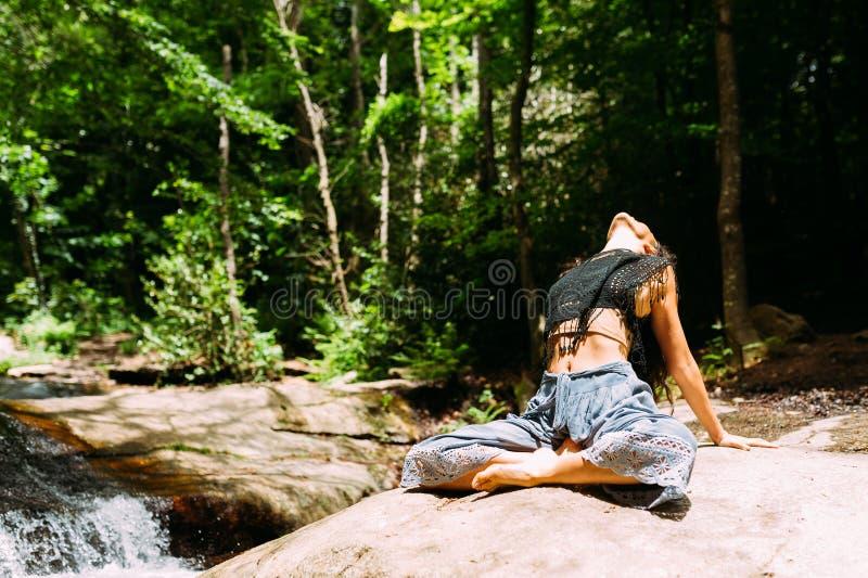 Feche acima da jovem mulher com o vestido oriental do estilo que faz a pose da ioga na pedra perto de um rio imergido na natureza fotografia de stock royalty free