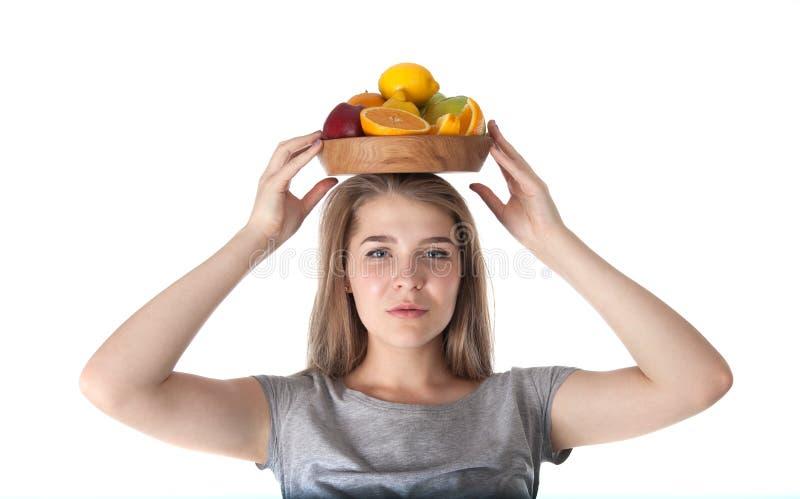 Feche acima da jovem mulher que está guardando uma bacia de madeira com frutos: maçãs, laranjas, limão Vitaminas e comer saudável foto de stock