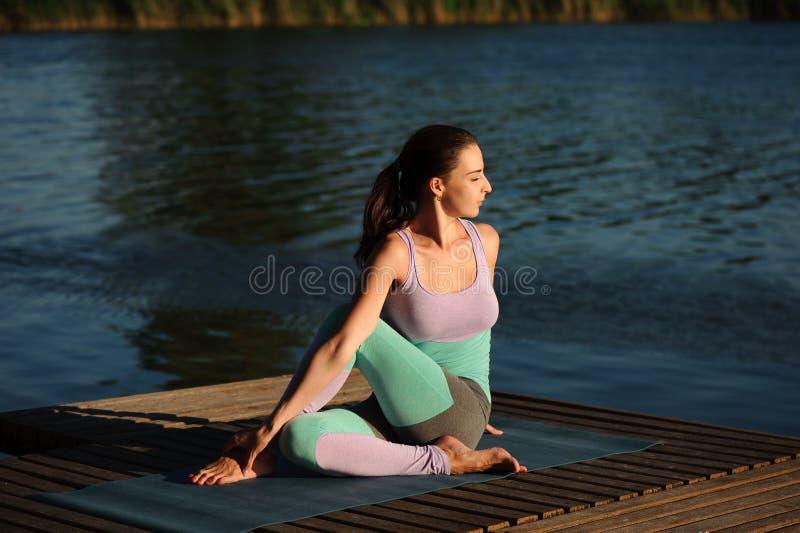 Feche acima da jovem mulher que faz a ioga no parque com por do sol fotografia de stock royalty free