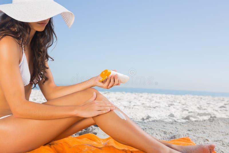 Feche acima da jovem mulher 'sexy' que aplica o creme do sol fotografia de stock