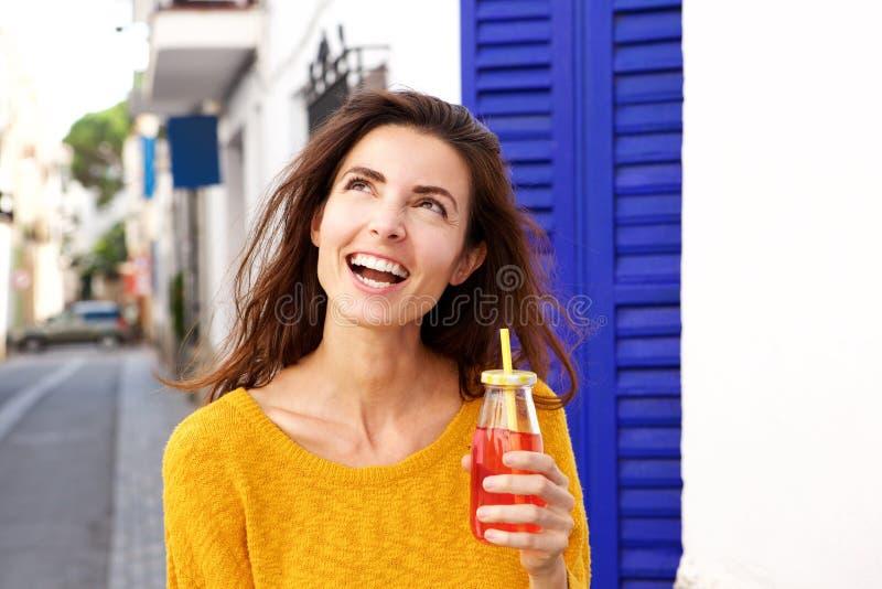 Feche acima da jovem senhora bonita que guarda o suco que olham ausente e o sorriso foto de stock royalty free