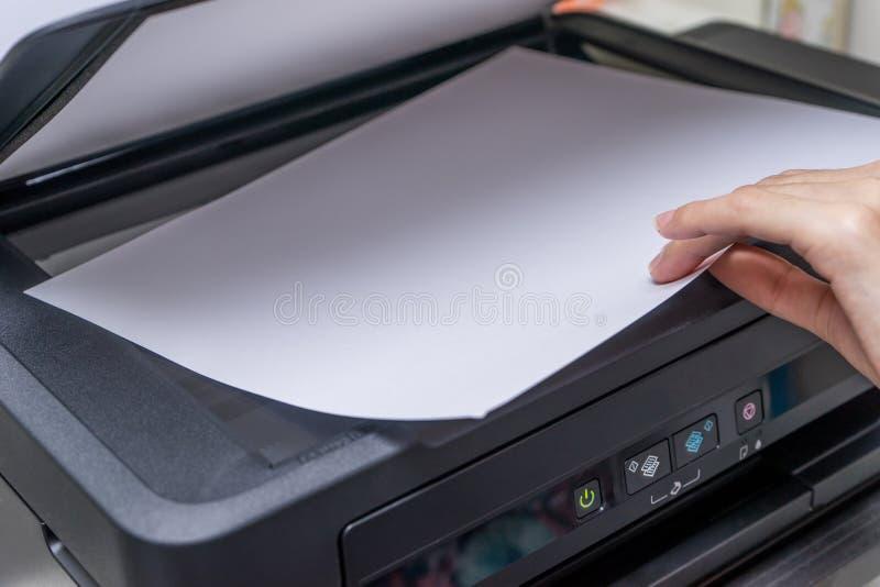 Feche acima da mão da mulher com copiadora de trabalho, impressora fotos de stock royalty free