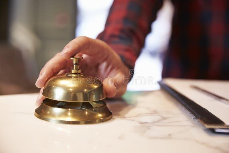 Feche acima da mão do convidado na recepção Bell do hotel imagem de stock
