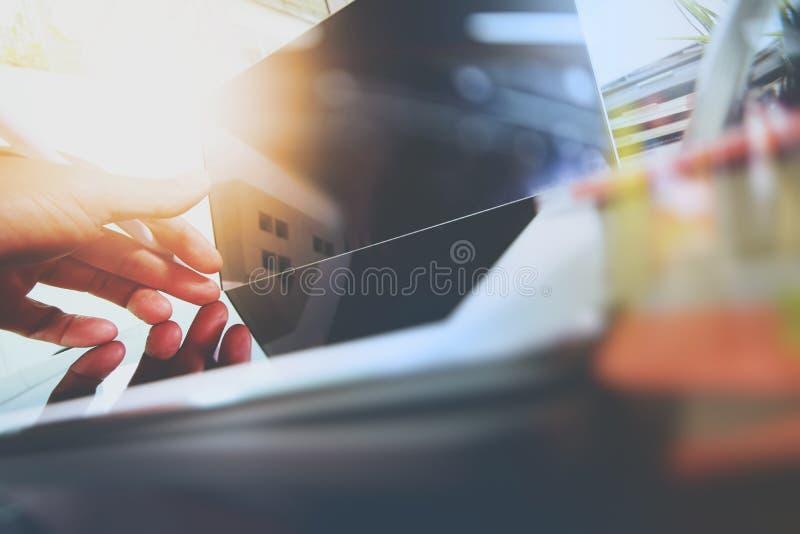 Feche acima da mão do desenhista que trabalha com o laptop em de madeira imagem de stock