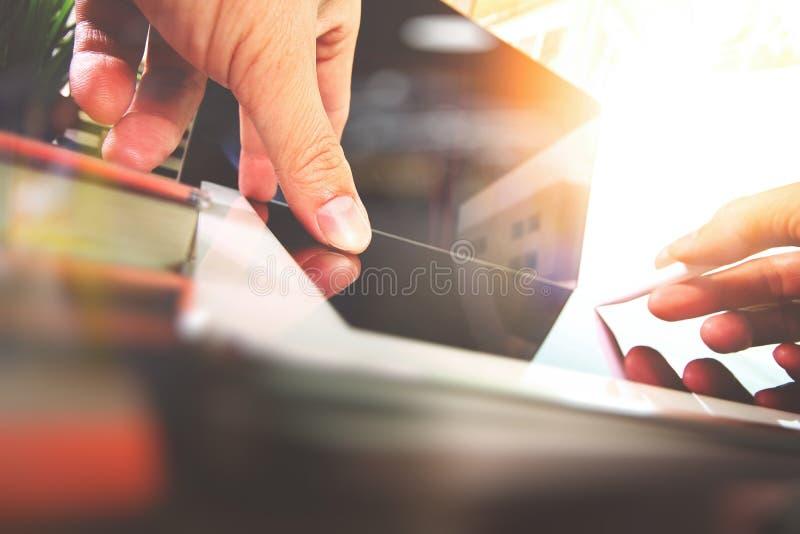 Feche acima da mão do desenhista que trabalha com o laptop em de madeira imagem de stock royalty free