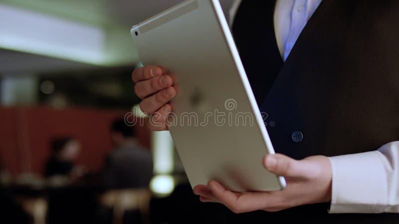 Feche acima da mão do garçom que nota abaixo do menu na tabuleta estoque Garçom com a tabuleta fotos de stock