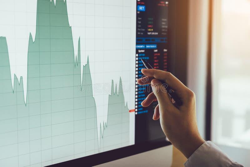 Feche acima da mão do homem de negócios que aponta à carta e à análise do mercado de valores de ação no tela de computador fotografia de stock