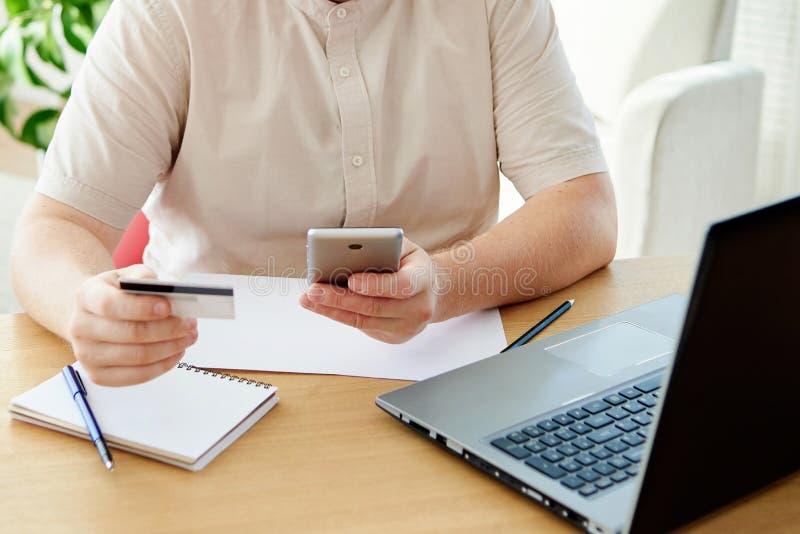 Feche acima da mão do homem que guarda o cartão de crédito e que paga a compra com o telefone esperto no escritório, espaço da có imagens de stock
