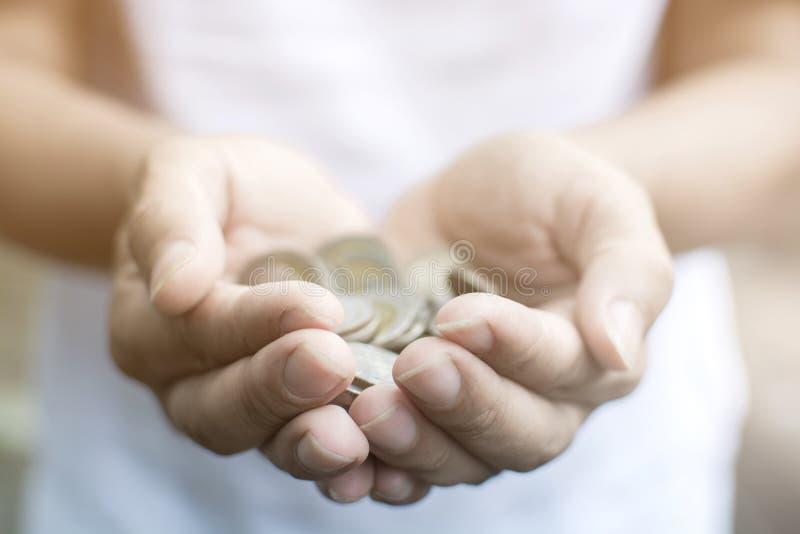 Feche acima da mão do homem que guarda uma pilha das moedas pela mão dois fotografia de stock