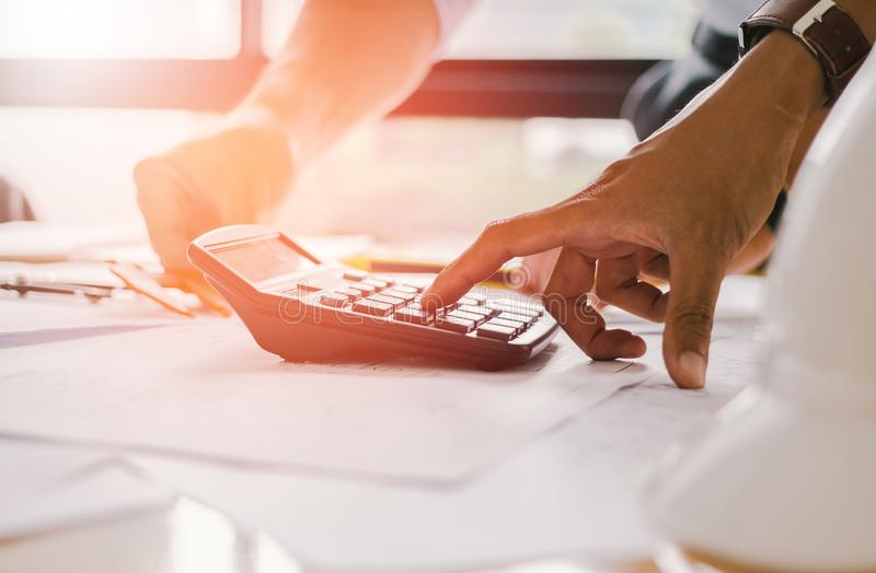 Feche acima da mão do homem usando bonusOr calculador da calculadora a outra compensação aos empregados para aumentar a produtivi fotografia de stock