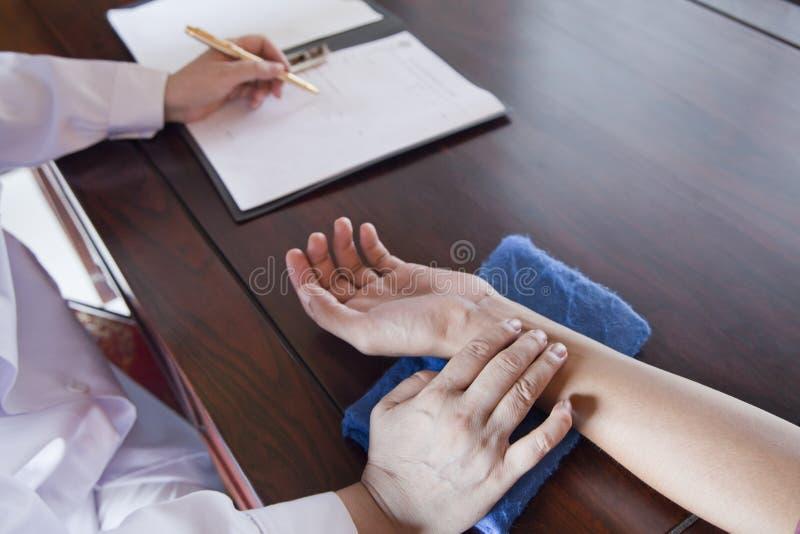 Feche acima da mão do paciente quando doutor Takes Pulse imagem de stock