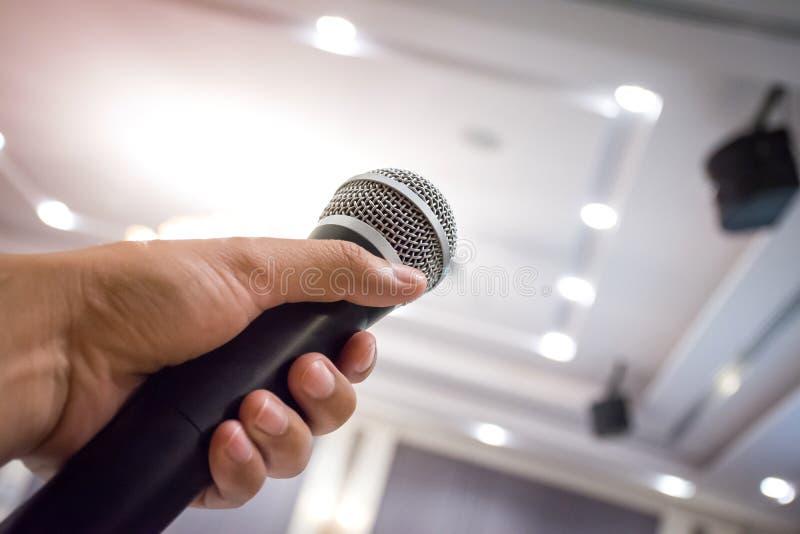 Feche acima da mão do ` s do homem que guarda o microfone na sala de conferências ou imagem de stock