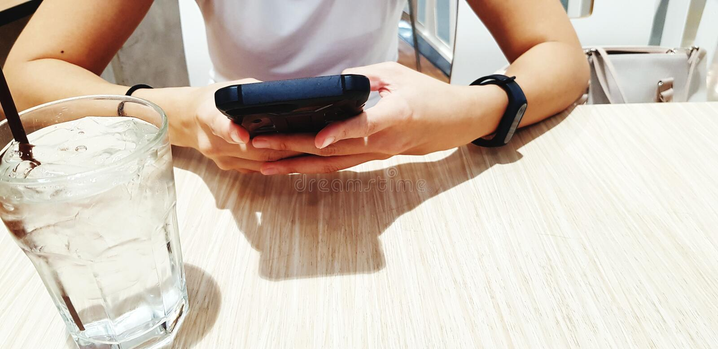 Feche acima da mão do ` s da mulher usando o telefone esperto preto com vidro da água fria na tabela de madeira durante o aliment fotos de stock royalty free