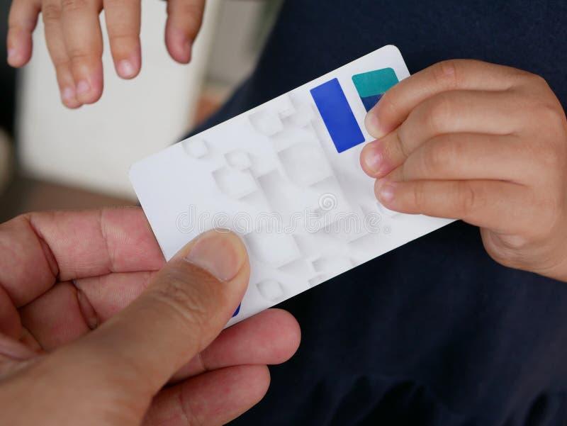 Feche acima da mão do ` s do pai que sustenta um ATM/cartão de crédito, não querendo deixar sua mão do ` s do bebê removê-la fotos de stock