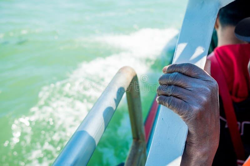 Feche acima da mão emigrante africana fina e magro do homem no barco ao cruzar o mar Mediterrâneo a Europa no dia ensolarado foto de stock royalty free